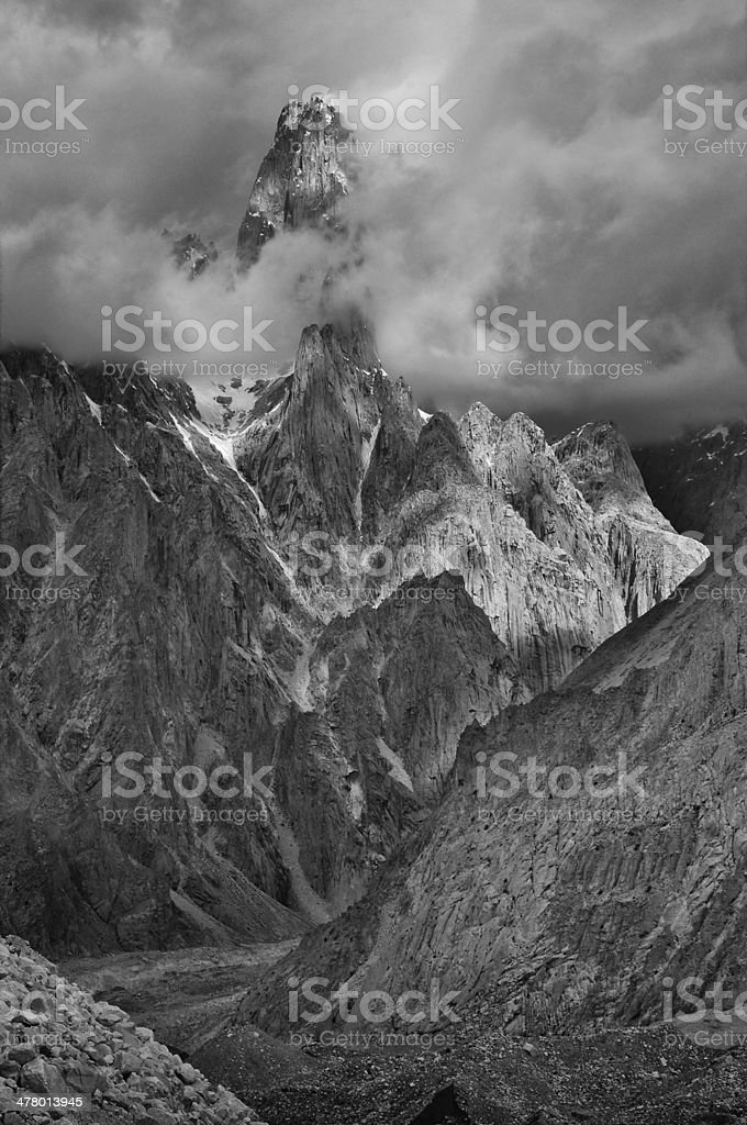 Trango Tower appearing through clouds stock photo