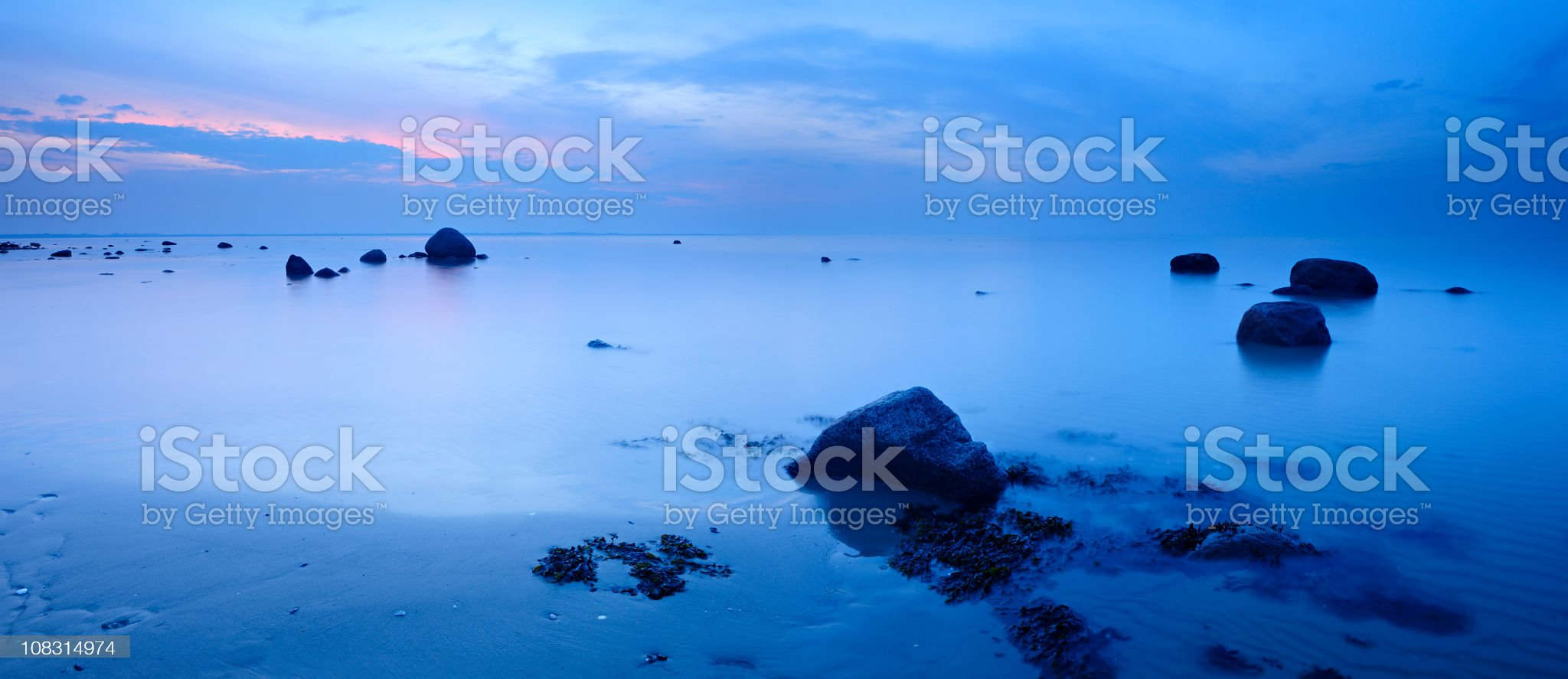 Tranquil Blue Sea with Huge Boulders at Sunset royalty-free stock photo