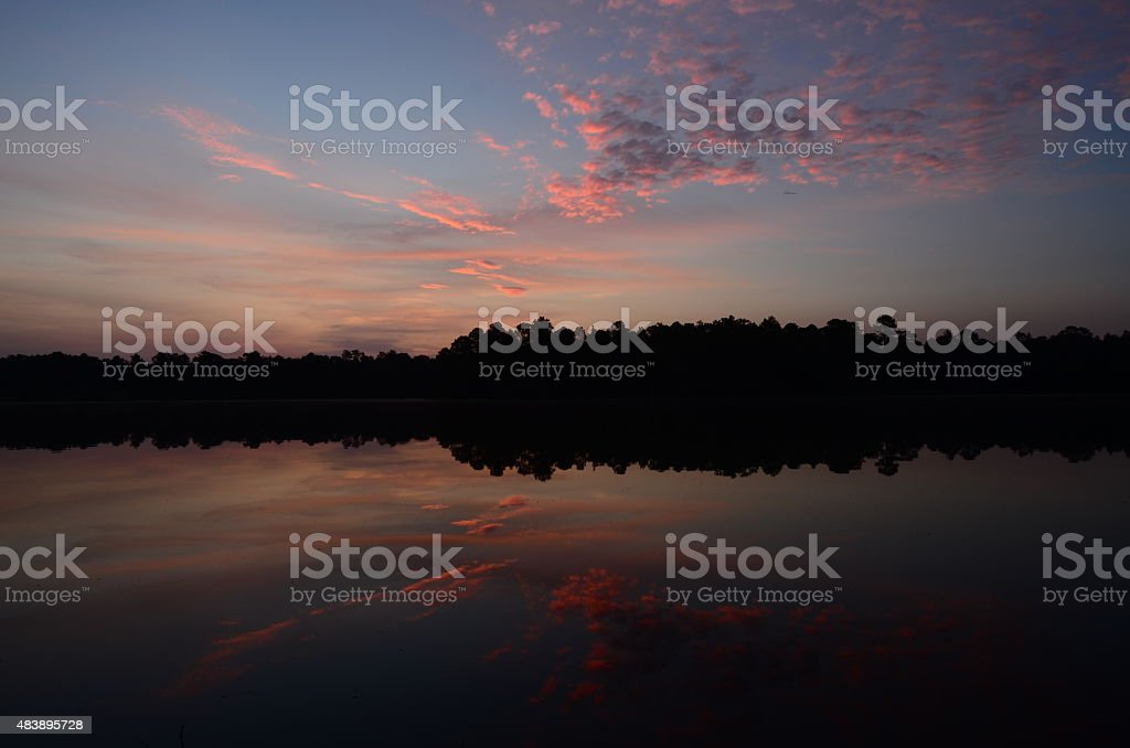 Tranquil cloudy sunset on lake with forest on horizon stock photo