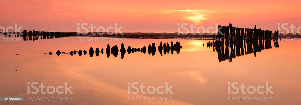 Tranquil Coastal Sunrise with old breakwater on the beach royalty-free stock photo