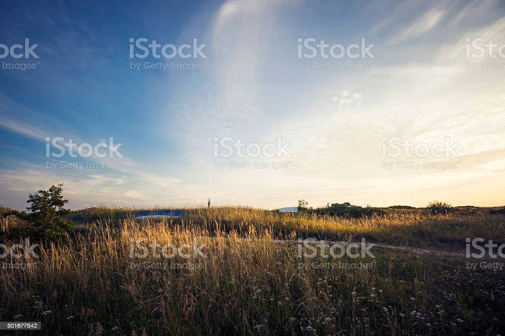 Tranquil evening sunset by calm beach meadow and rowboat (XXXLarge) stock photo