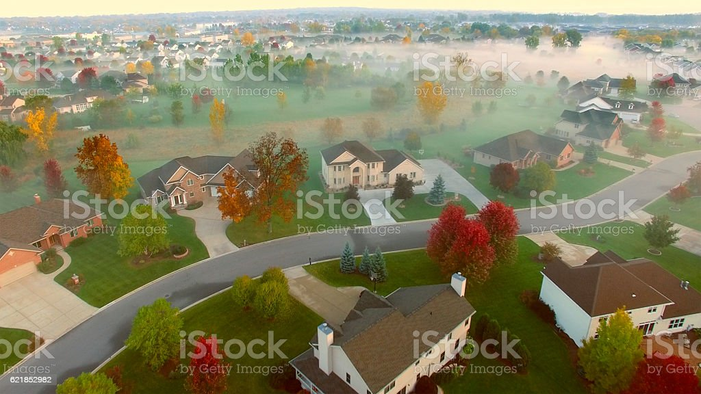 Tranquil idyllic neighborhood shrouded in fog at dawn stock photo