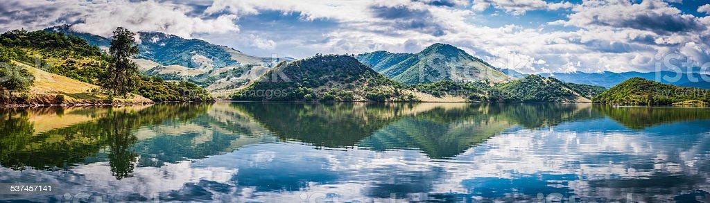 Tranquil lake reflecting green mountain shore Emigrant Lake panorama Oregon stock photo