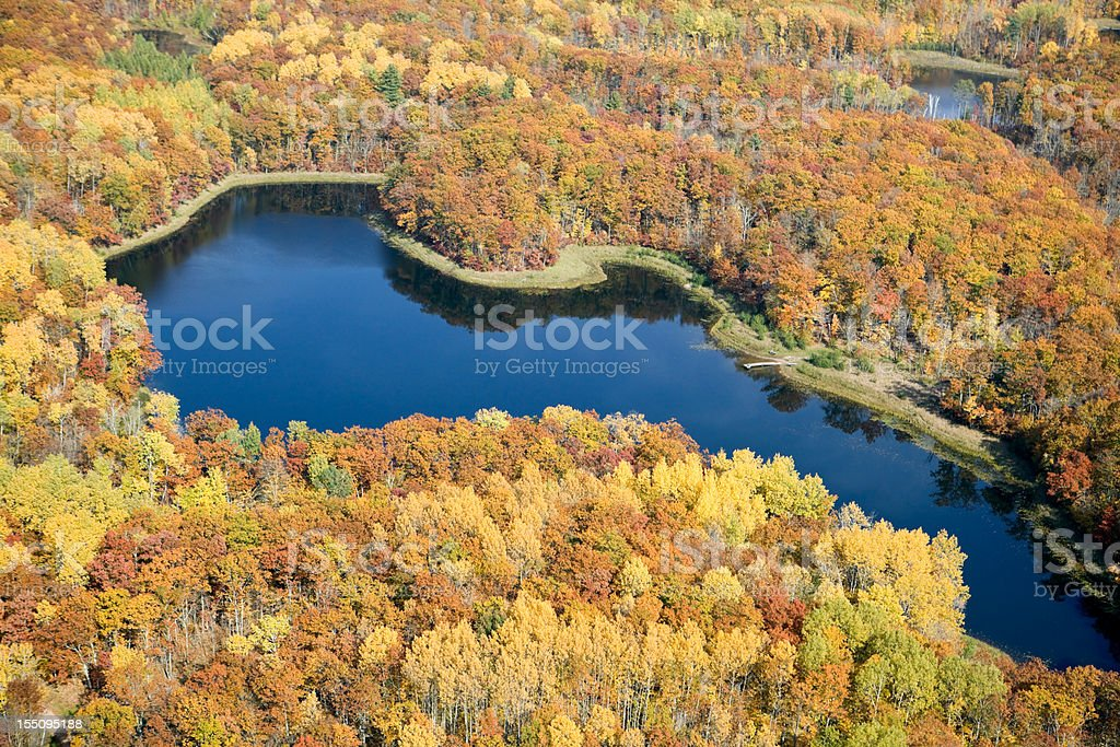 Tranquil Lake with Dock Surrounded by Fall Trees Aerial stock photo