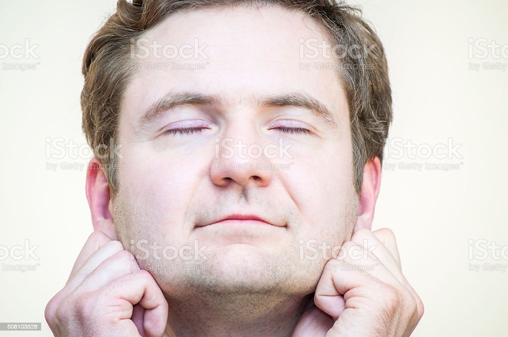 Tranquil, meditating man holding his earlobes on white background stock photo