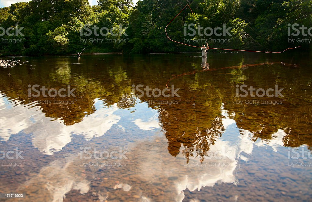 Tranquil river scene with two fly fisherman casting royalty-free stock photo