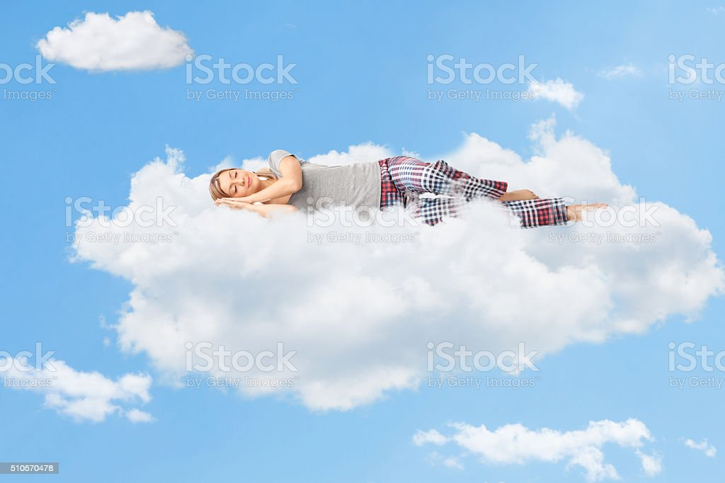 Tranquil scene of a woman sleeping on cloud stock photo