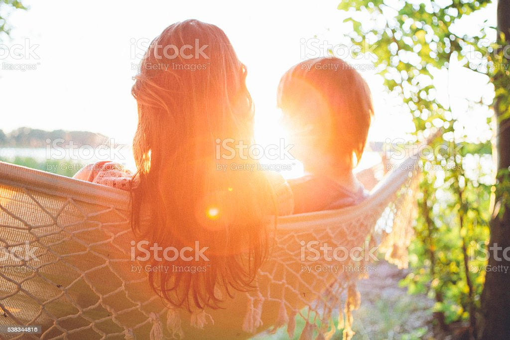 tranquil scene: rear view, couple relax in hammock, lens flare stock photo