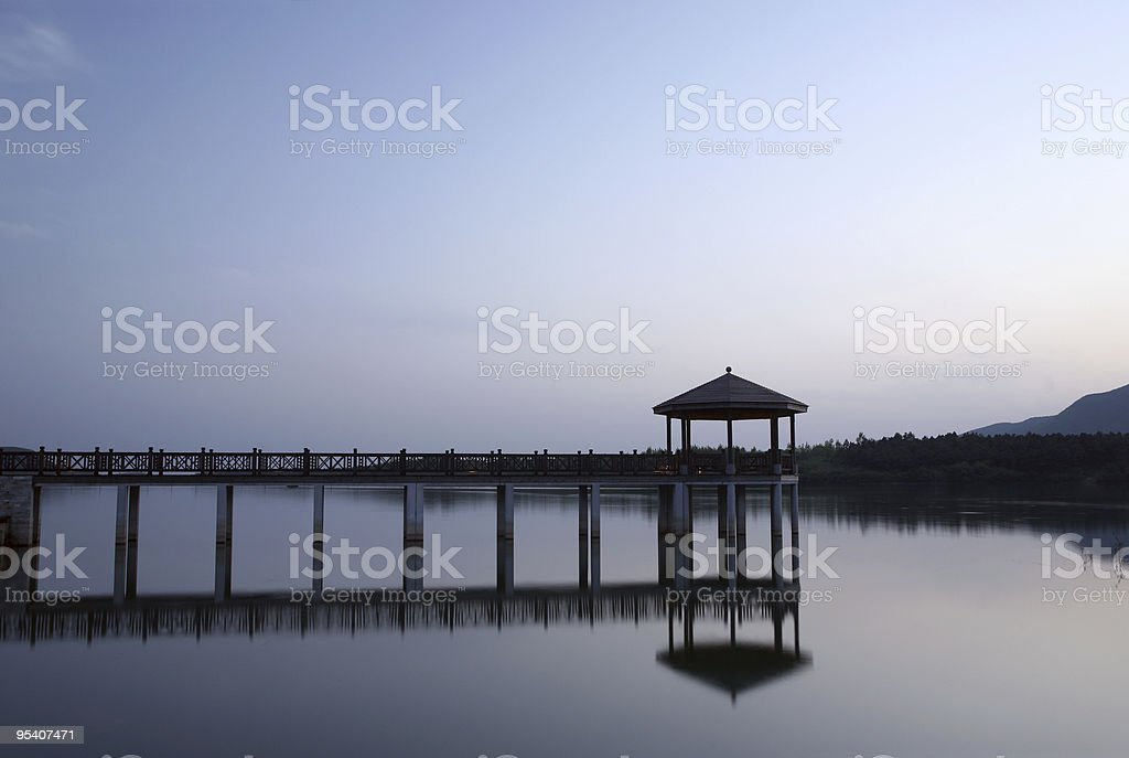 Tranquil scenery of waterside with pavilion and footbridge stock photo