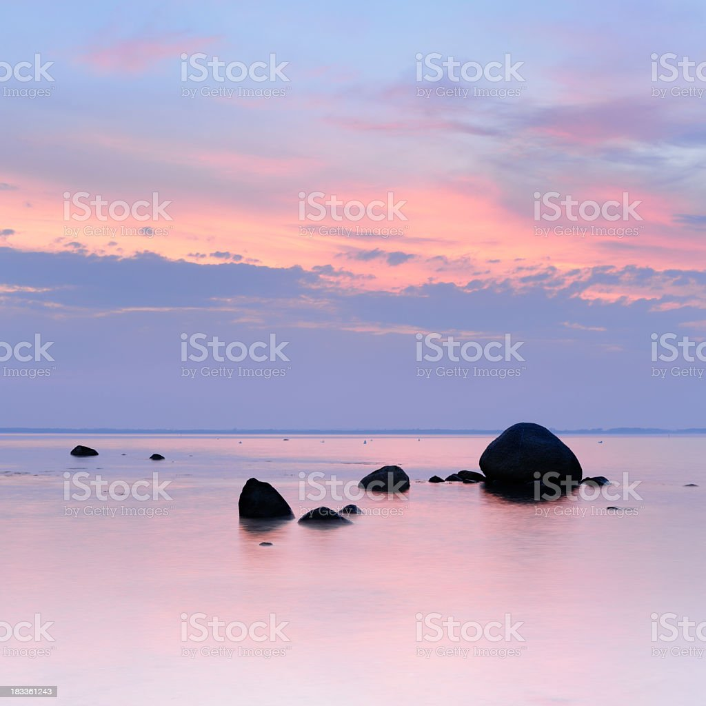 Tranquil Silver Sea with Huge Boulders at Dusk royalty-free stock photo