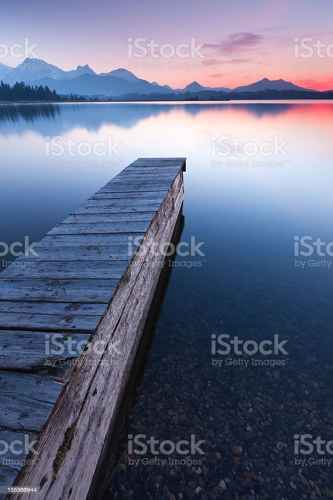 tranquil sunset at lake bannwaldsee with jetty, bavaria - germany stock photo