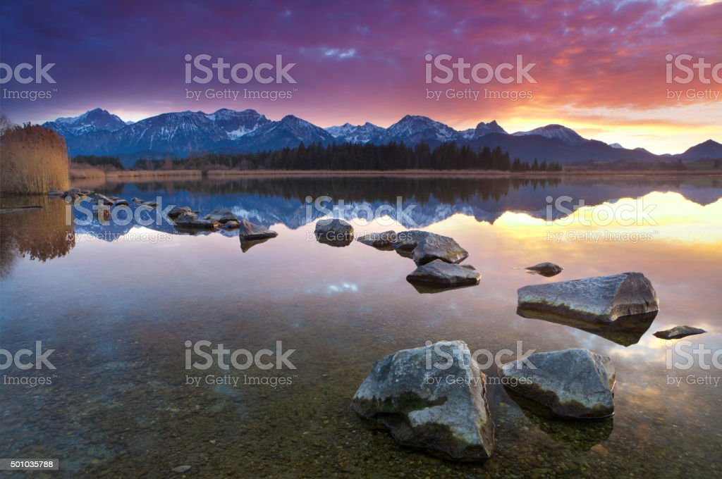 tranquil sunset at lake hopfensee, bavaria, allgaeu, germany stock photo