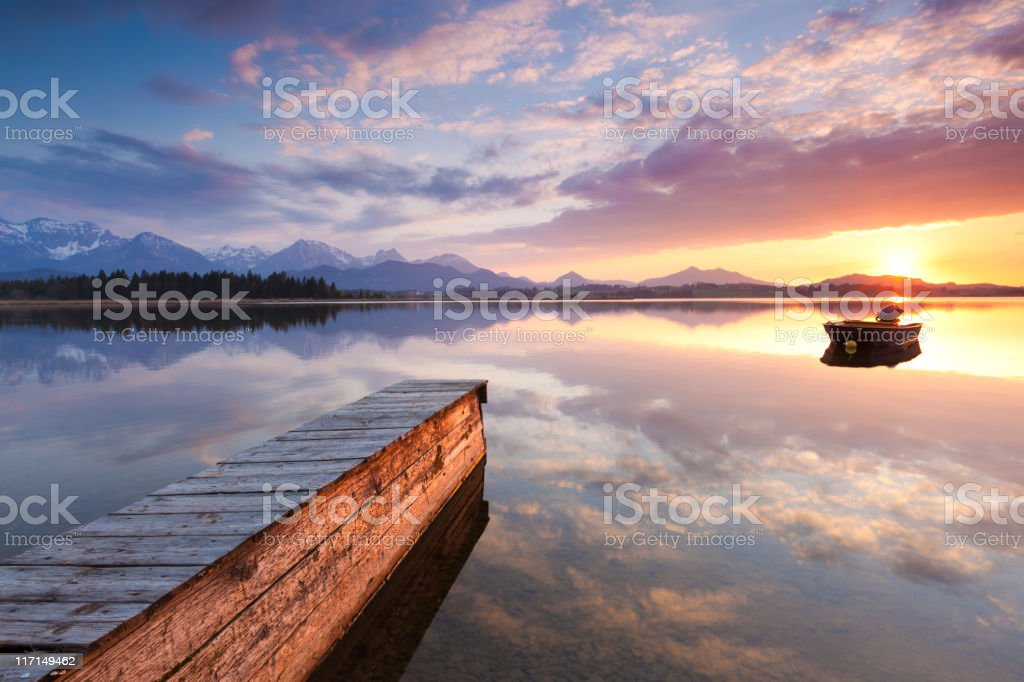 tranquil sunset at lake hopfensee, bavaria with jetty, boat, germany royalty-free stock photo