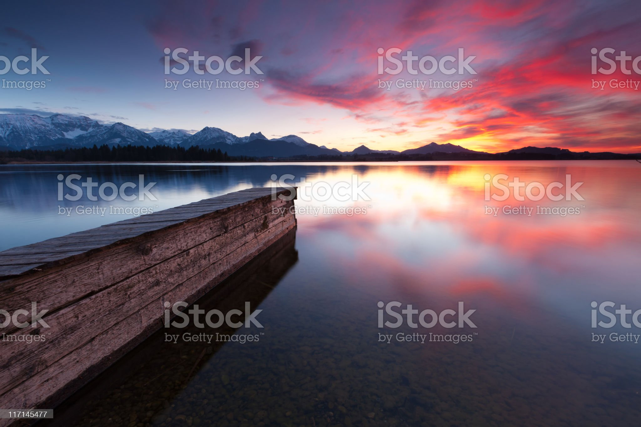 tranquil sunset at lake hopfensee in bavaria with pier- germany royalty-free stock photo