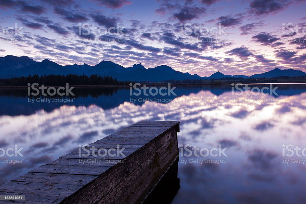tranquil sunset at lake hopfensee in bavaria with pier- germany stock photo