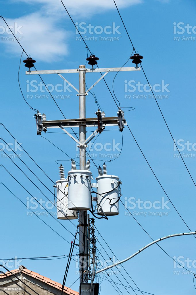 Transformers on a street post with power lines stock photo