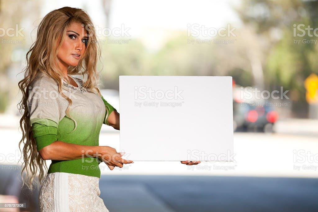 Transgender female holding blank poster board sign stock photo