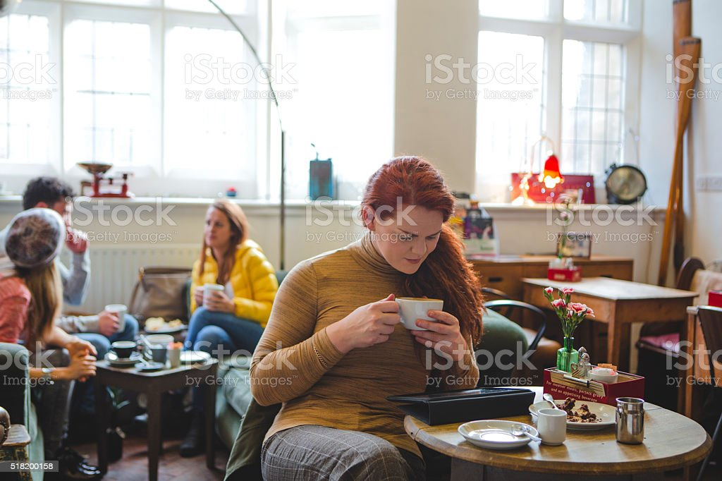 Content with a coffee and her digital tablet stock photo