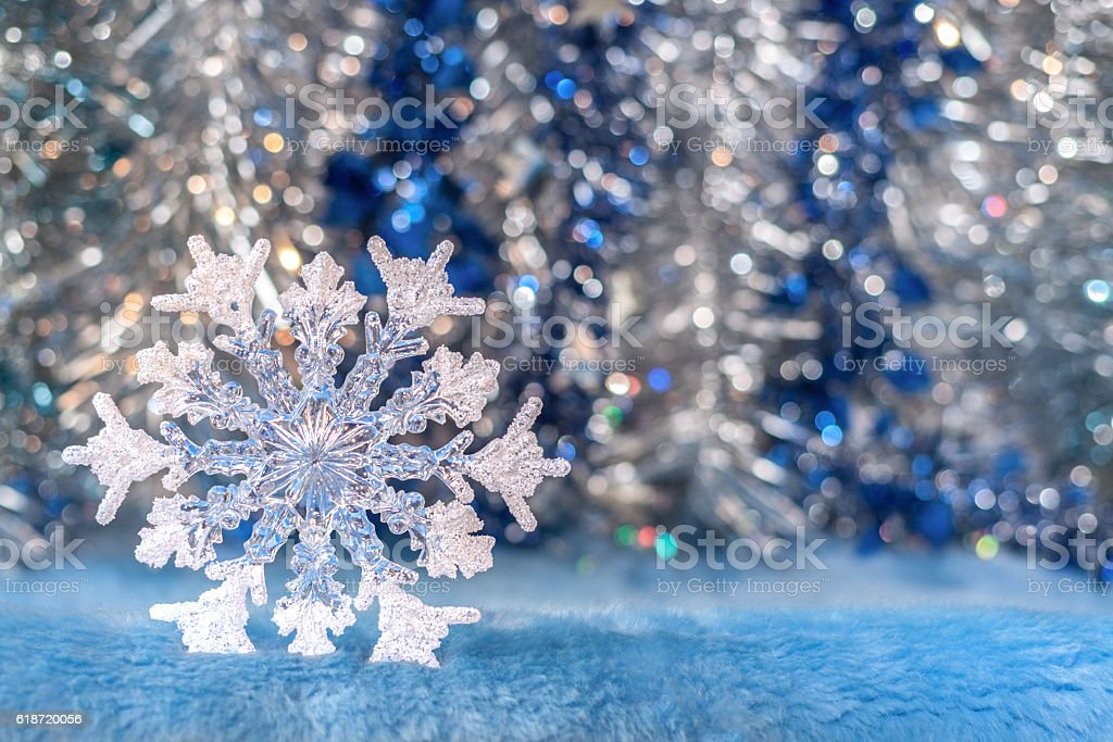 Translucent Christmas toy snowflake on silver-blue bokeh background. stock photo