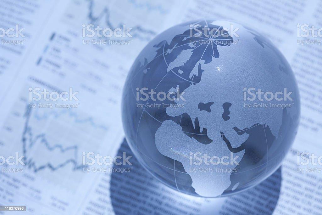 Translucent globe resting over economic data stock photo