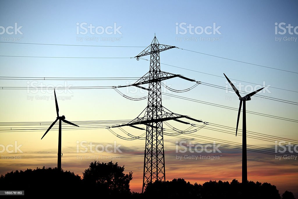 Transmission Tower and Windcraft sillouette at dusk stock photo