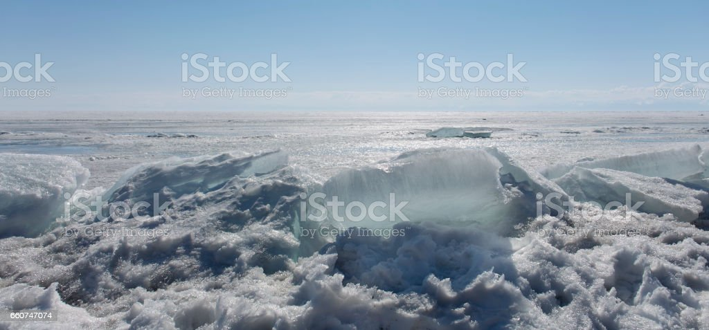 Transparent blue ice hummocks on lake Baikal shore. Siberia winter landscape view. Snow-covered ice of the lake. Big cracks in the ice floe. stock photo