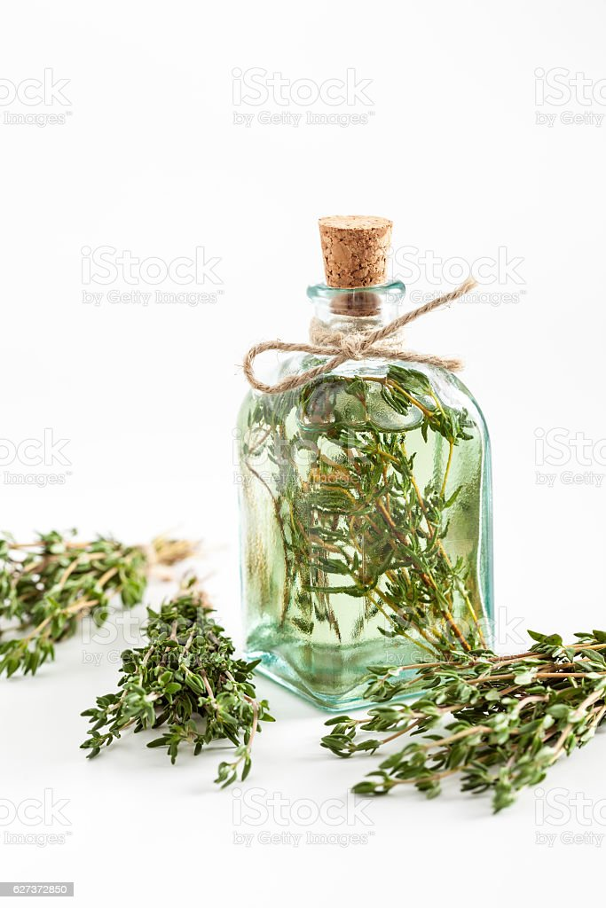Transparent bottle of thyme essential oil or infusion and herbs stock photo
