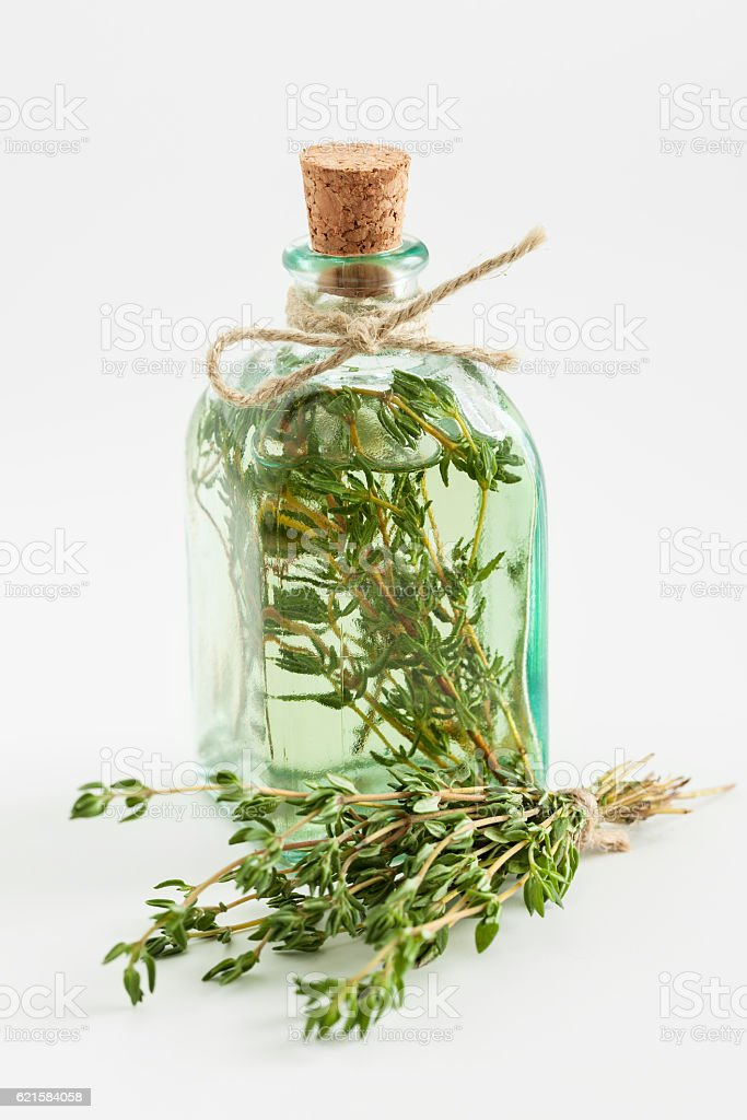 Transparent bottle of thyme essential oil or infusion stock photo