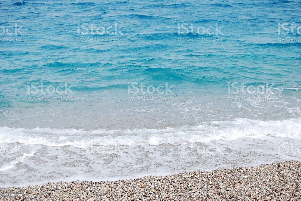 transparent deep blue wave of sea that breaks on seashore stock photo