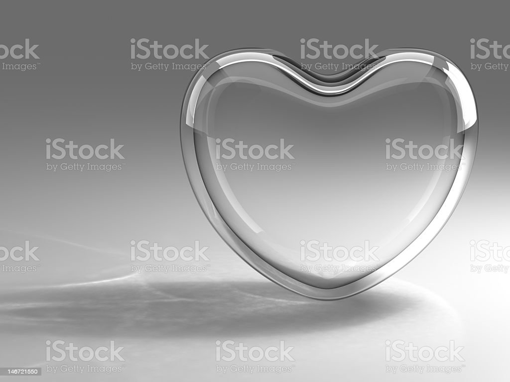 A transparent glass heart is balanced on its edge  stock photo