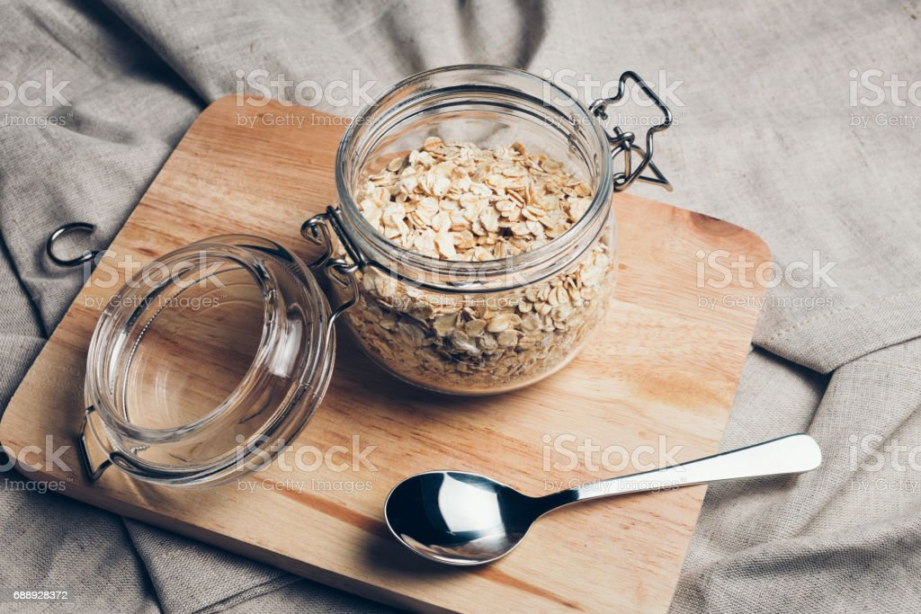 Transparent glass jar with rolled oats stock photo