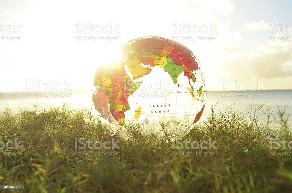 transparent globe on grass and bright sunbeam stock photo