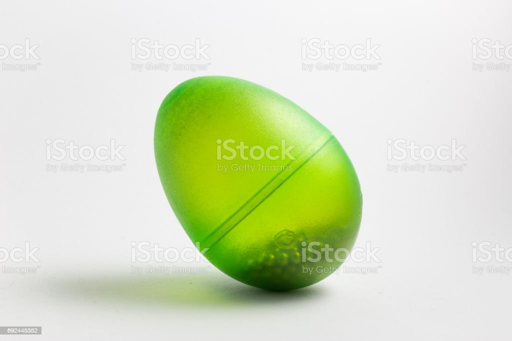 Transparent green egg shaker with beads inside stock photo