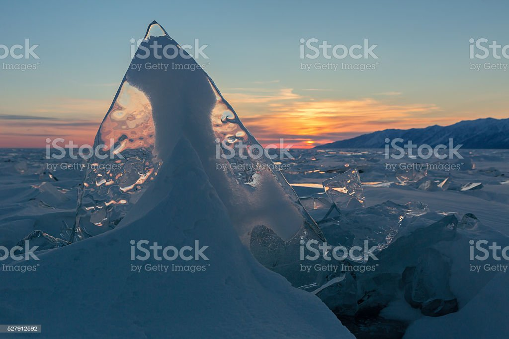 Transparent ice on sunset sky background stock photo