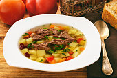 Transparent meat soup with bean and vegetables.