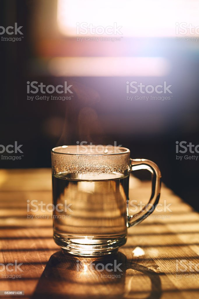 Transparent mug with hot water on kitchen stock photo