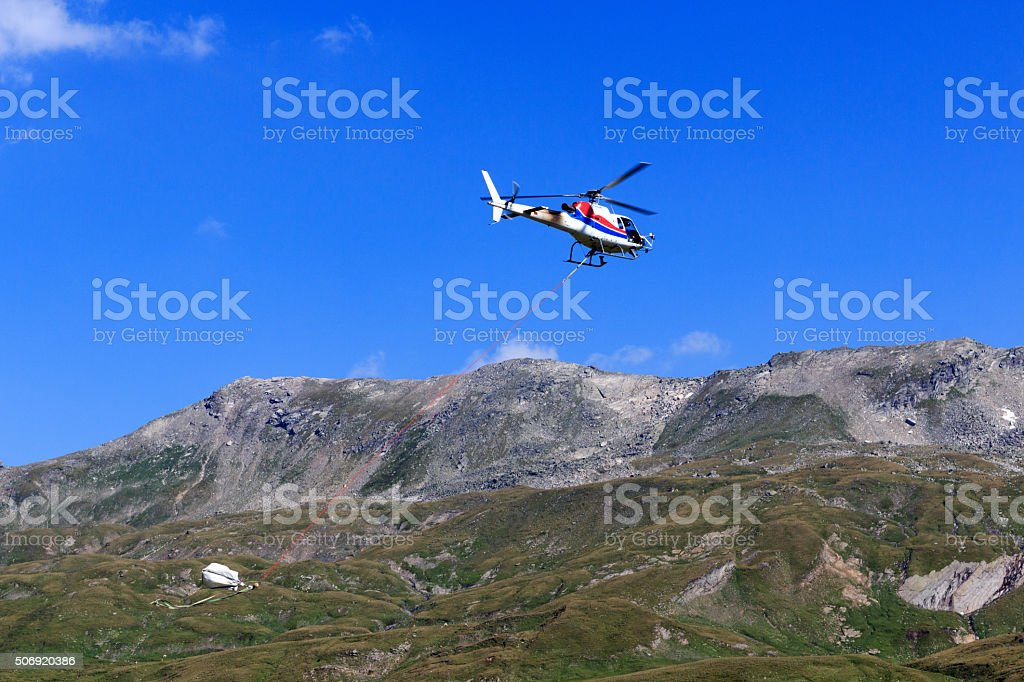 Transport helicopter flying and mountain panorama, Hohe Tauern Alps stock photo