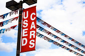Transportation:  'Used Cars' sign over a dealership car lot.