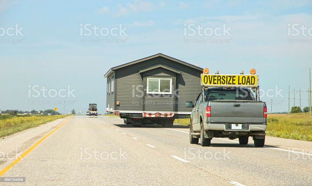 Transporting a House Trailer Down a Highway on Flatbed Truck stock photo