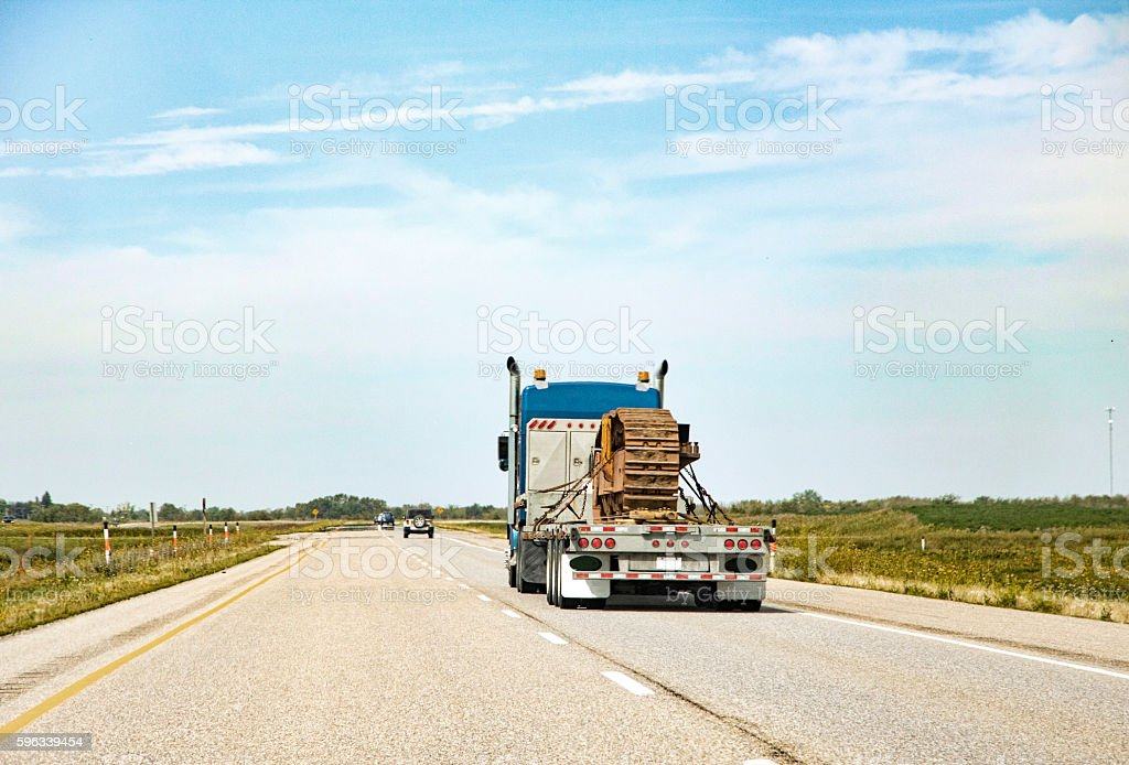 Transporting Bulldozer Tracks Down a Highway on Flatbed Truck stock photo