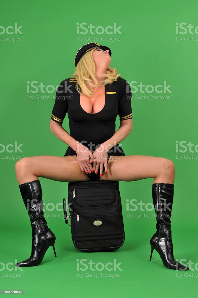 Transsexual airline pilot wearing sexy boots on a green screen stock photo