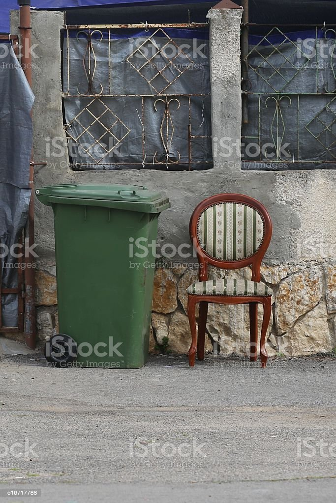 Trash Can next to a Padded Chair on the Sidewalk stock photo