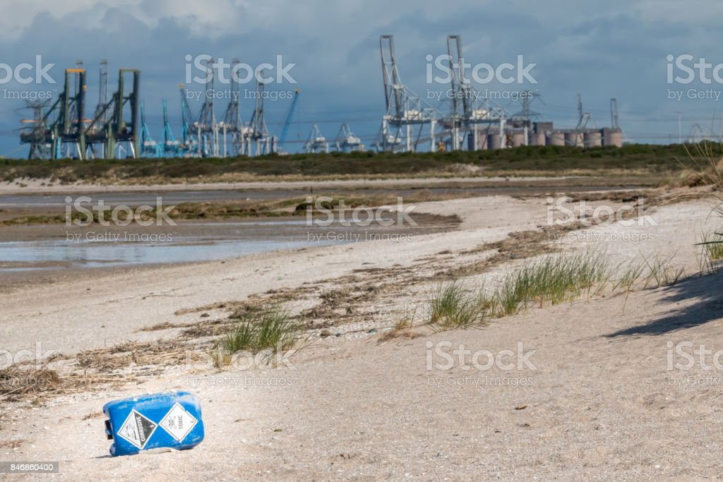 trash on the beach with cranes in the background stock photo