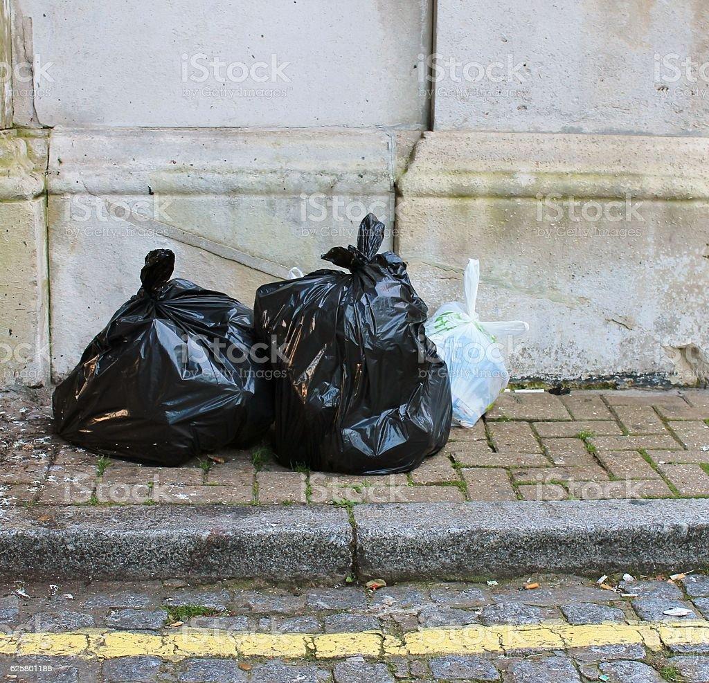 Trash rubbish outside against brick stock photo
