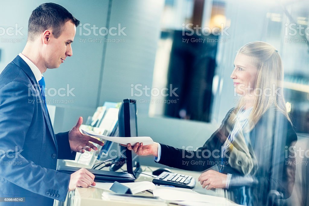Travel agent handing travel plan to a man in suit stock photo