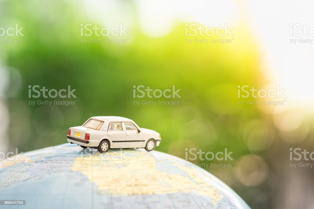 Travel and transport concept. Miniature Toy car on world map balloon with green nature as background. stock photo