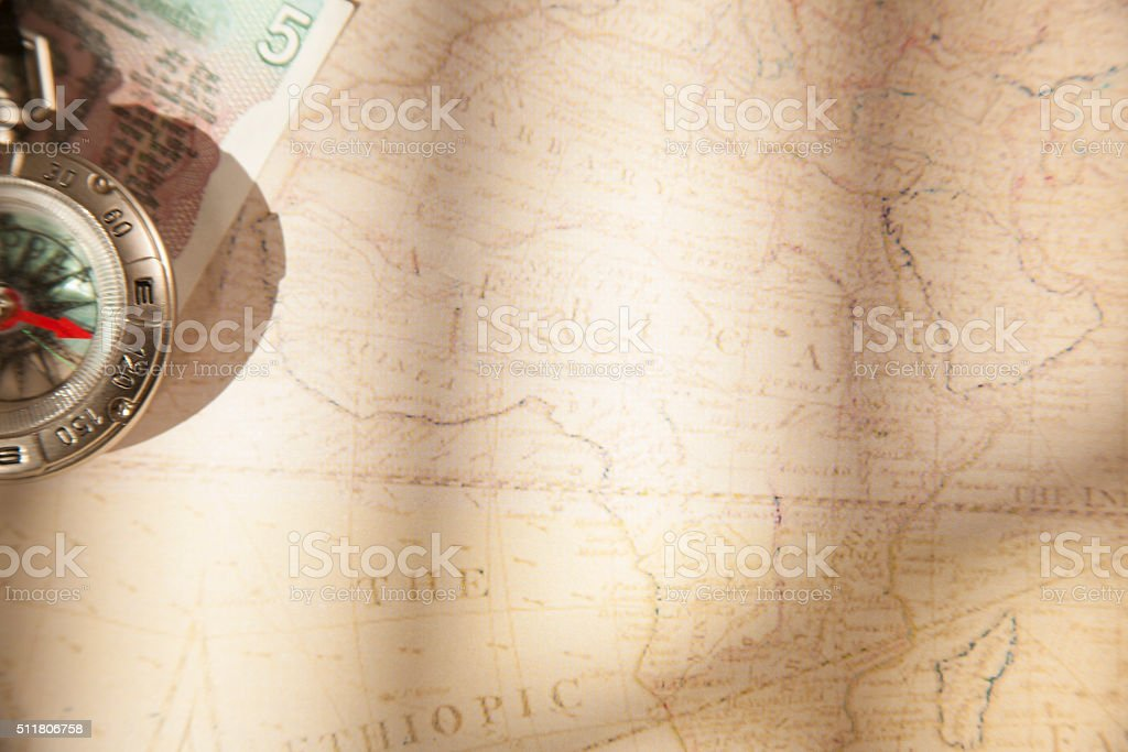 Travel background. Compass, money on top of world map. stock photo