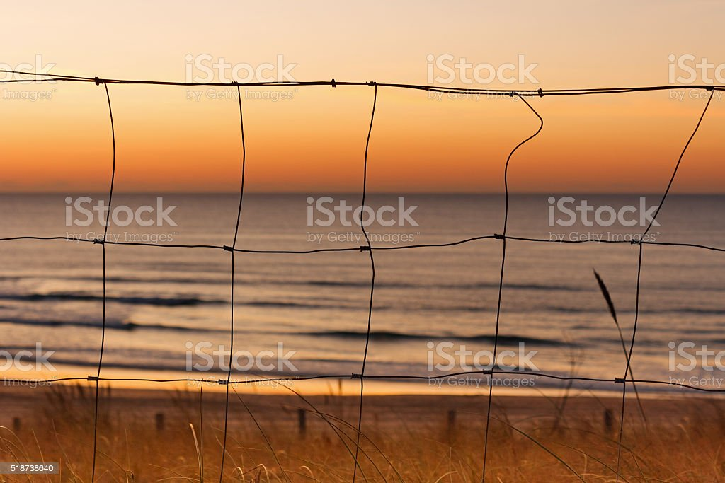 Travel background: Fence in sunset at the beach of Mimizan-Plage stock photo