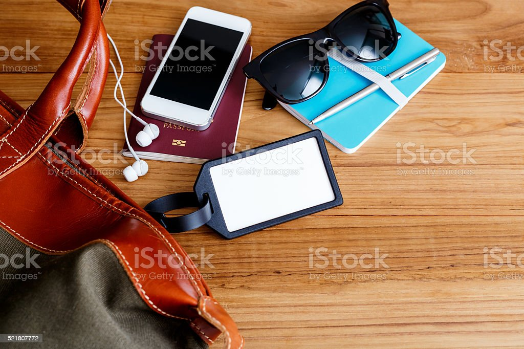 Travel bag and blank tag on wood table stock photo