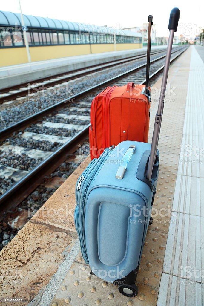 Travel bags stands on platform near railway tracks. royalty-free stock photo